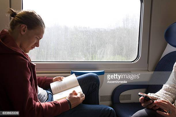 young man reads on train, while another texts - train interior stock pictures, royalty-free photos & images