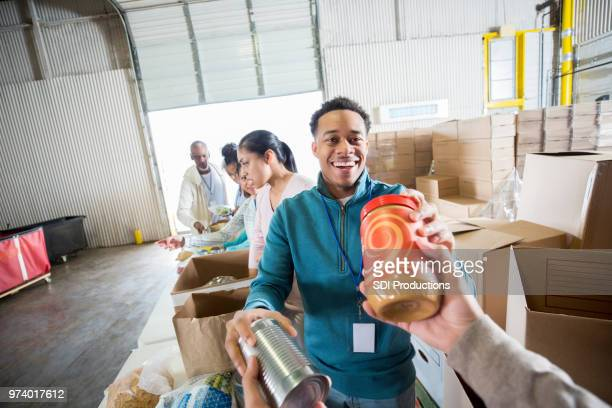 young man receives food donations in food bank - food bank stock pictures, royalty-free photos & images