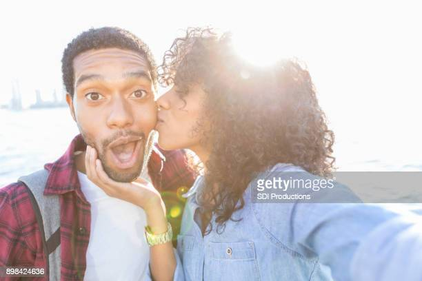 young man receives thank you kiss from wife on vacation - heterosexual couple stock pictures, royalty-free photos & images