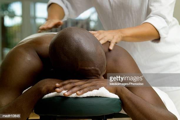 young man receiving a back massage - masaje hombre fotografías e imágenes de stock