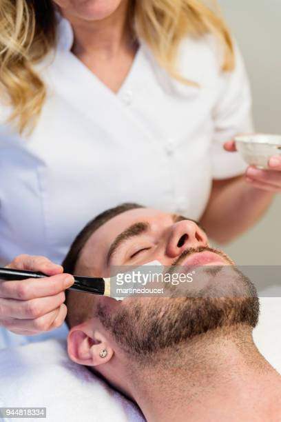 Young man receiving a facial treatment in beauty spa.