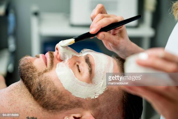 "young man receiving a facial treatment in beauty spa. - ""martine doucet"" or martinedoucet stock pictures, royalty-free photos & images"