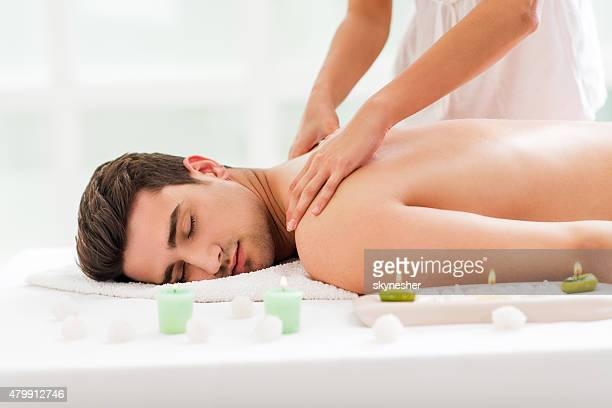 Young man receiving back massage at spa.