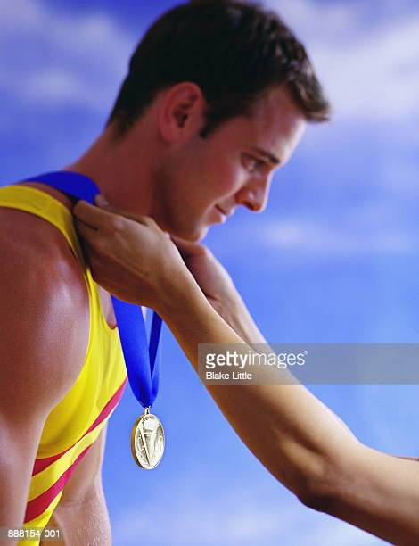 young man receiving gold medal, profile, close-up - awards ceremony stock pictures, royalty-free photos & images