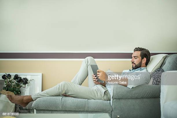young man reclining on hotel room chaise longue using digital tablet, dubai, united arab emirates - chaise longue stock photos and pictures