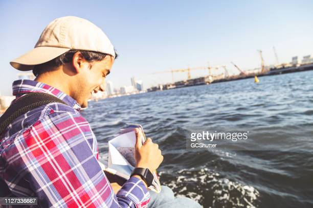 young man referring map and crossing dubai creek to his next tourist destination - inexpensive stock photos and pictures
