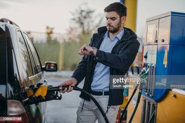 young man refueling gas at the gas station - gas station stock pictures, royalty-free photos & images