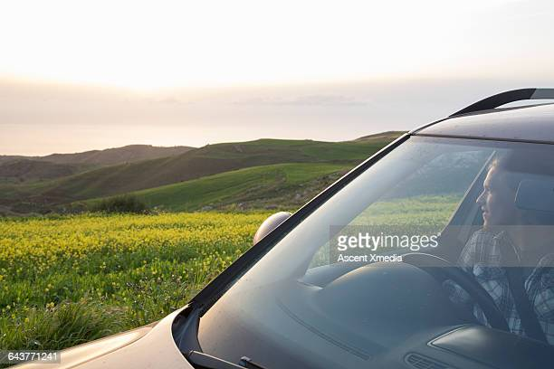 Young man relaxes in vehicle, looks out over field