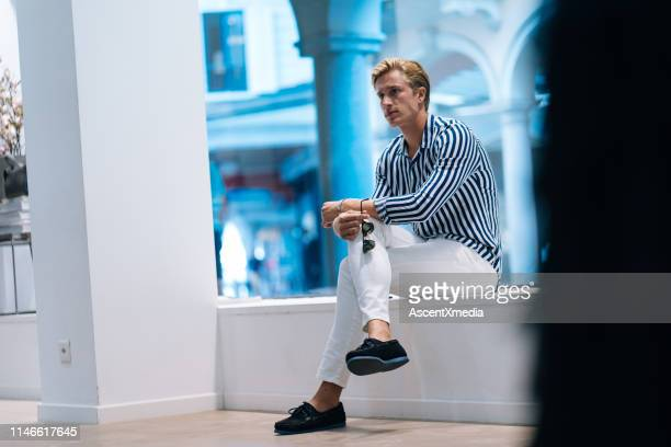 young man relaxes on bench - striped pants stock pictures, royalty-free photos & images