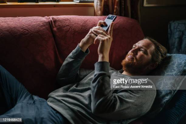 Young man relaxes on safa, sends text
