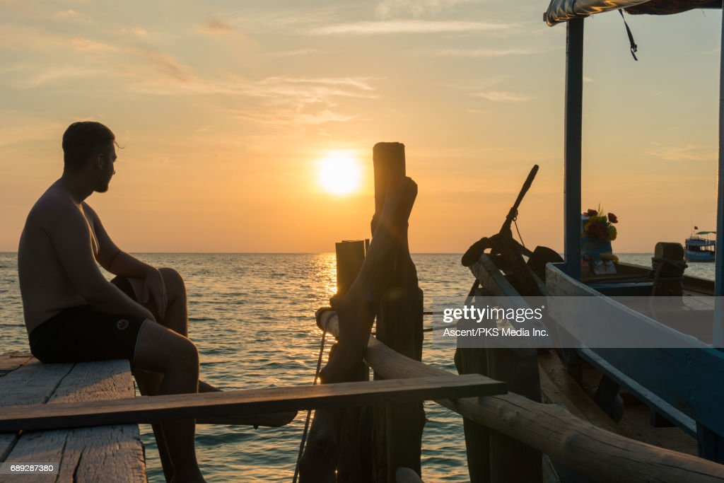 Young man relaxes on wooden deck at sunset : Stock Photo