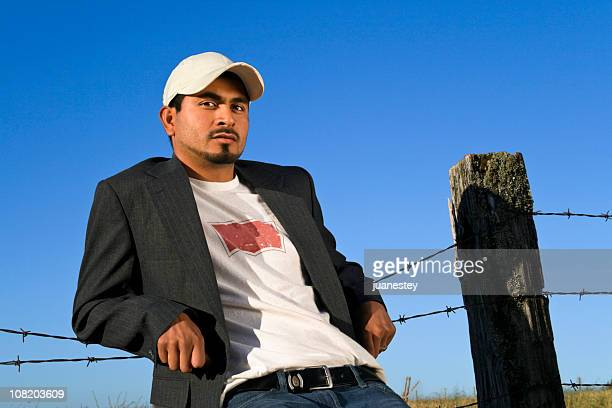Young Man Relaxing Against Fence