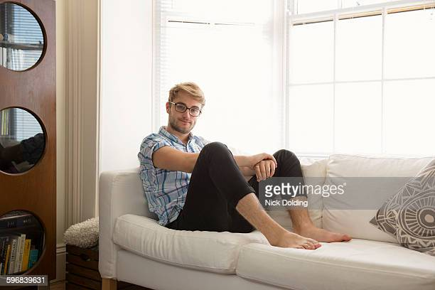 young man relaxing at home - mens bare feet stock photos and pictures