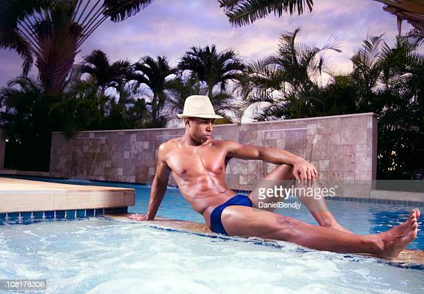 young man relaxing by swimming pool - black men in speedos stock photos and pictures