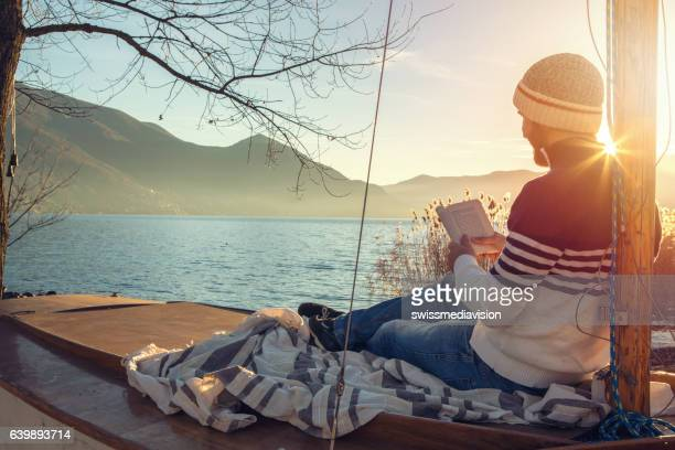 Young man relaxing by the lake, reading book