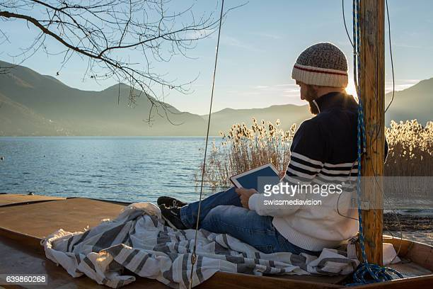 Young man relaxing by the lake with digital tablet