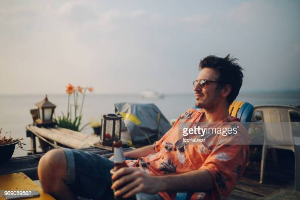 young man relaxing by the ocean, having a beer, looking at sunset at koh lanta, thailand - hawaiian shirt stock photos and pictures