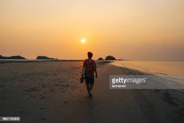 Junger Mann am Meer entspannen, den Sonnenuntergang auf der schönen Insel Koh Lanta, Thailand