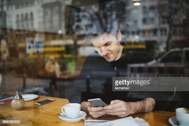 Junger Mann zum Entspannen in einem Café in Berlin, SMS auf dem Handy