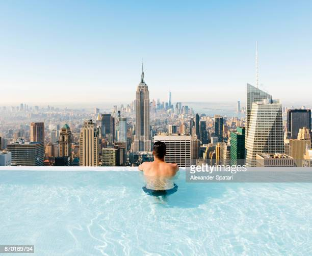 young man relaxing in a swimming pool with view towards new york city skyline - poolside stock pictures, royalty-free photos & images