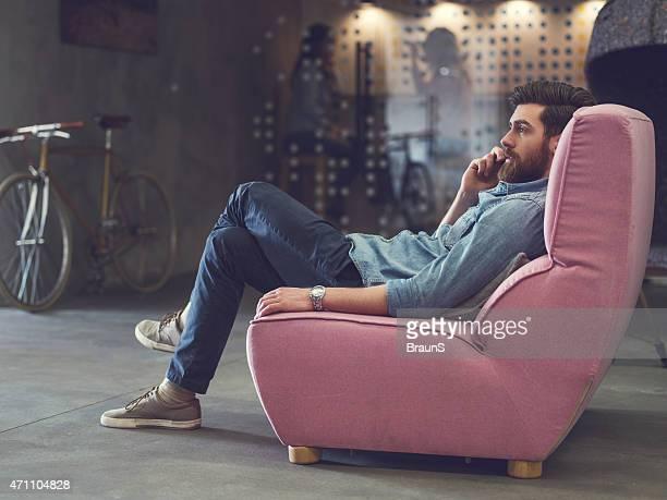 若い男性のアームチェアでリラックスして、電話で話している。