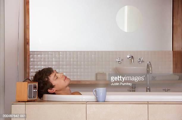 Young man relaxing in bath, side view