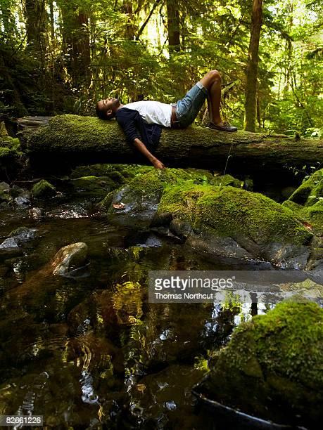 Giovane uomo rilassante nella foresta
