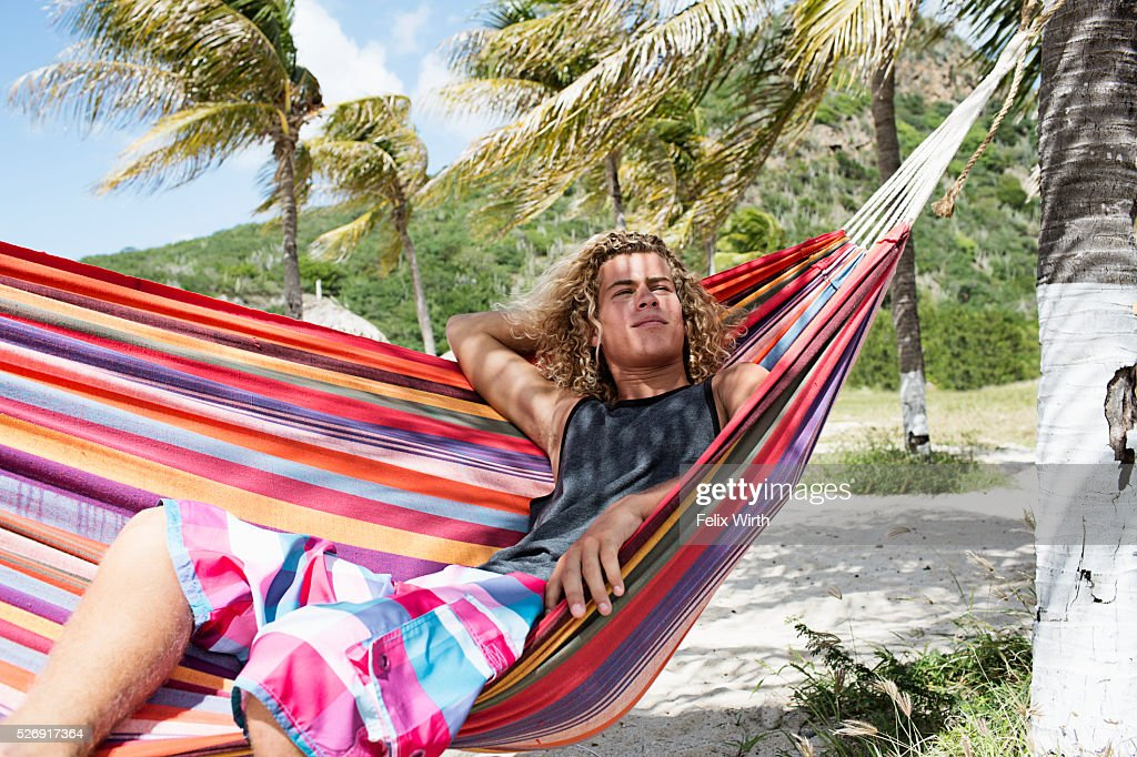 Young man relaxing in hammock on beach : Bildbanksbilder