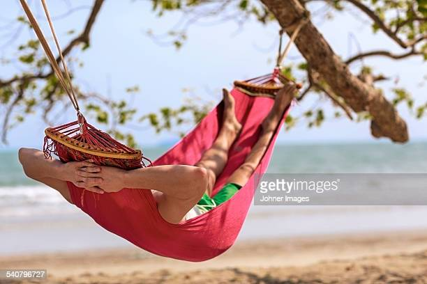 Young man relaxing in hammock on beach