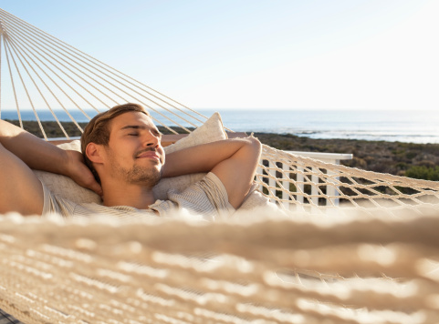 Young man relaxing in hammock with eyes closed - gettyimageskorea