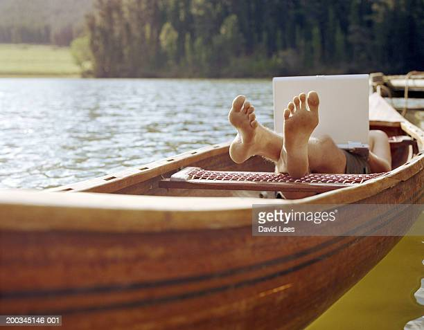 young man relaxing in small boat, using laptop, low section - mujeres fotos stock pictures, royalty-free photos & images