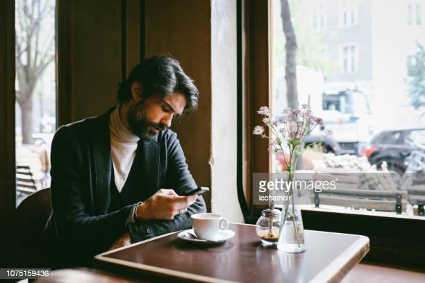 カフェでリラックスして、ベルリンでエスプレッソを持つ若い男 - プレンツラウアーベルグ ストックフォトと画像