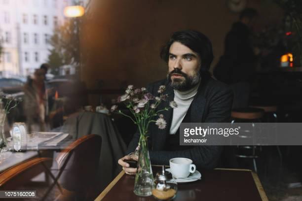 若い男がベルリンのカフェでリラックス - プレンツラウアーベルグ ストックフォトと画像