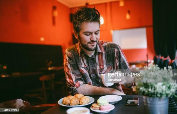 Jonge man ontspannen in het café, met espresso en croissants