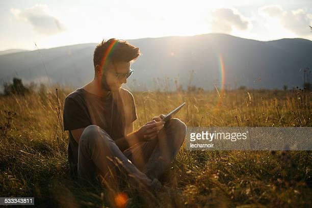 Junger Mann in der Natur entspannen und lesen