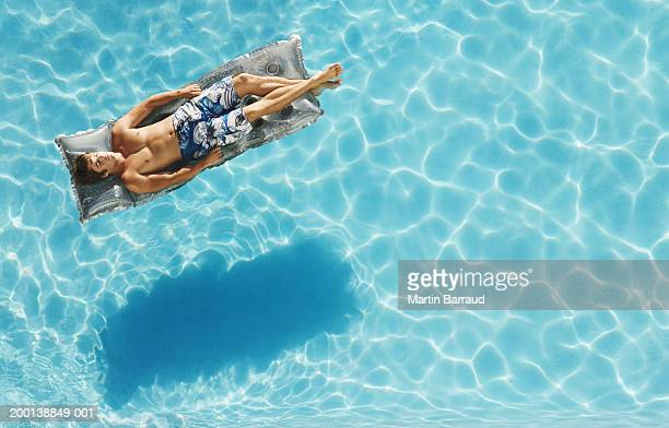 Young man relaxing on air bed, floating in pool, elevated view
