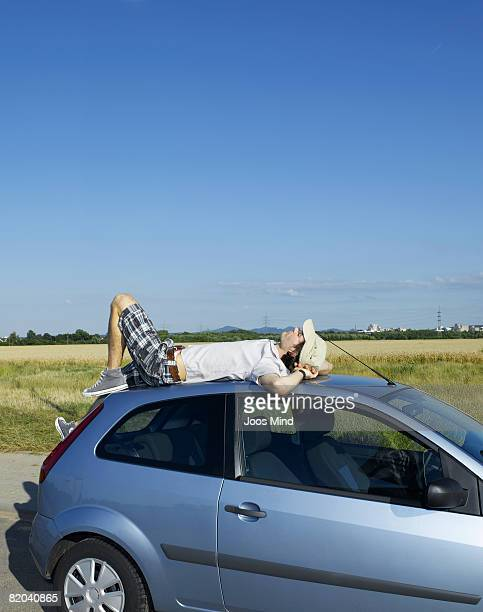 young man relaxing on car roof