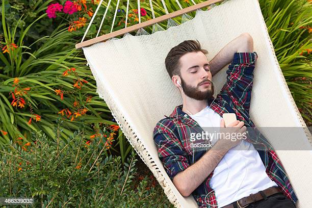 Young Man Relaxing on Hammock Listening to Music