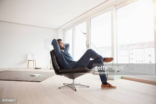 young man relaxing on leather chair in his living room - sitting stock pictures, royalty-free photos & images