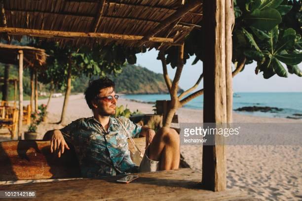 jovem muito relaxante na praia da ilha koh lanta, tailândia - table top - fotografias e filmes do acervo