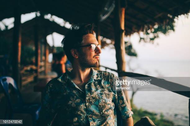young man relaxing on the beach of the koh lanta island, thailand - hawaiian shirt stock photos and pictures