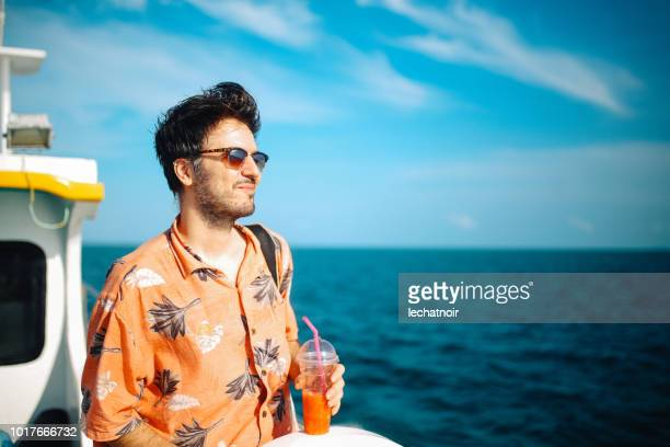 young man relaxing on the boat while traveling in between thai islands - hawaiian shirt stock photos and pictures