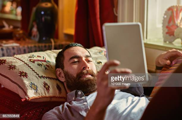 young man relaxing with a digital tablet - reading stock pictures, royalty-free photos & images