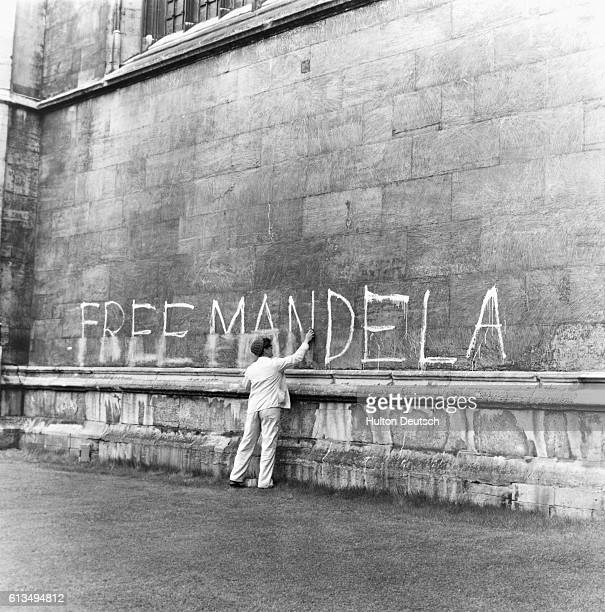 A young man removes graffiti reading 'Free Mandela' from a wall of King's College Chapel in Cambridge England in 1965 Nelson Mandela was imprisoned...