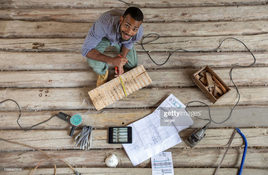 Young man renovating old floor : Stock Photo