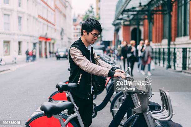 Young man renting bicycle on street in London