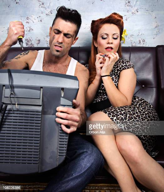 young man repairing television while woman paints nails - stereotypical homemaker stock pictures, royalty-free photos & images