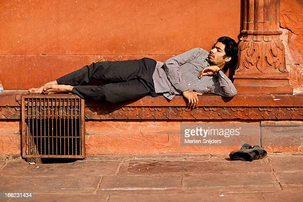 young man resting at mosque ledge - jama masjid delhi stock pictures, royalty-free photos & images