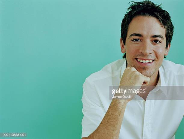 Young man resting chin on hand, smiling, portrait