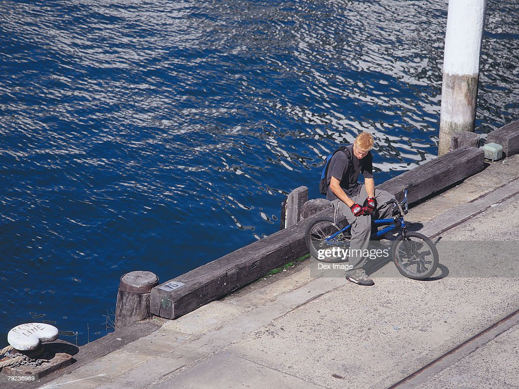 Young man resting on BMX on pavement : Stock Photo